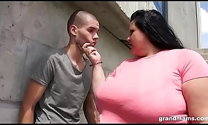 Heavy grandma deepthroats young boy outdoors