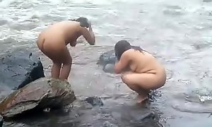 2992477 two indian full-grown womens bathing upon river naked