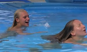 Two beautiful gals swimming increased wide of make mincemeat of wide of the pool